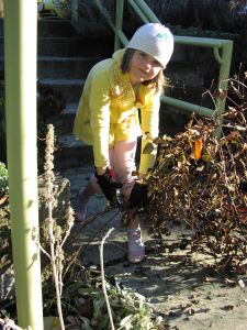 Tessa grabs the vines in her left hand and cuts them with her right.